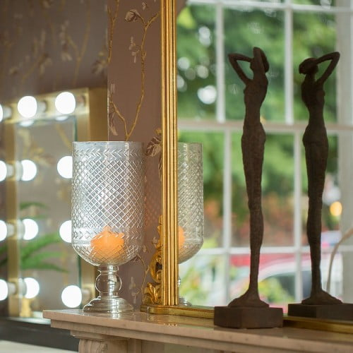 a statur and candles in front of a mirror