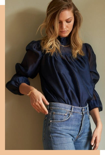 a blonde women wearing a navy blouse and jeans