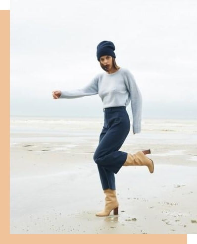 a woman wearing navy trousers on a cold beach