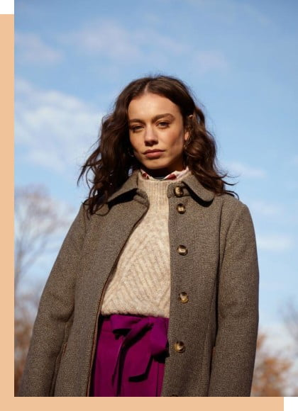 a woman wearing a tweed style coat with a blue sky in the background