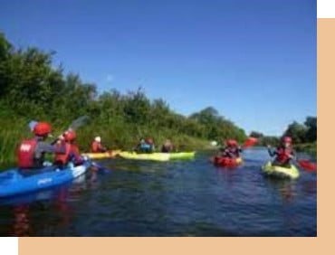 a group of people kayaking on a river in ireland